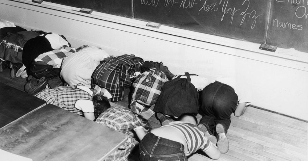 1950s children practicing duck and cover for bomb warnings
